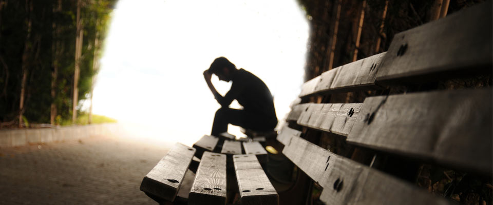 Silueta de un hombre sentado en un parque al atardeceres, solo y cabizbajo.