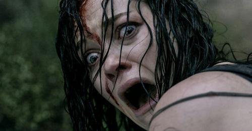 Mujer con el pelo mojado y cara ensangrentada, con expresión de miedo y gritando.