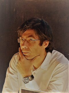 Fotografía del escritor Ruy Vega, que aparece con el pelo semi largo, gafas sin montura, sin barba, camisa blanca y la mano puesta en la cara en actitud pensante.